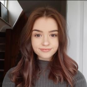 Teenager with auburn hair smiling at camera